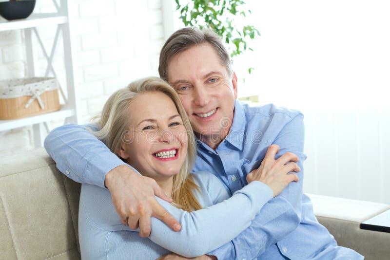Ευτυχές ερωτευμένο αγκάλιασμα ζευγών μεταξύ τους στο κρεβάτι στο σπίτι στοκ φωτογραφίες