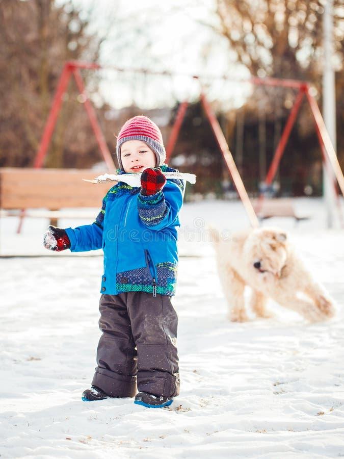 Ευτυχές λευκό καυκάσιο αγόρι μικρών παιδιών που τρέχει και που παίζει με το χιόνι και το άσπρο μεγάλο μεγάλο σκυλί κατοικίδιων ζώ στοκ φωτογραφία