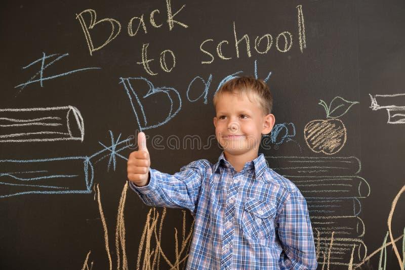 Ευτυχές ευρωπαϊκό αγόρι στο σχολικό πίνακα με την επιγραφή πίσω στο σχολείο στοκ φωτογραφίες