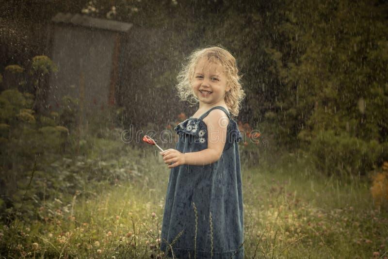Ευτυχές εύθυμο κορίτσι παιδιών που χαμογελά κάτω από την ευτυχή ξένοιαστη παιδική ηλικία έννοιας επαρχίας βροχής στην επαρχία στοκ εικόνα