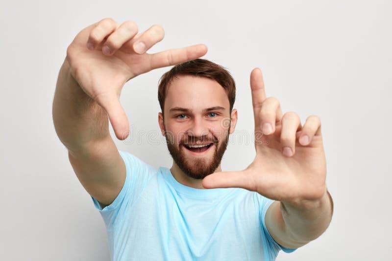 Ευτυχές εύθυμο όμορφο άτομο που κάνει το πλαίσιο με τα χέρια του στοκ φωτογραφία