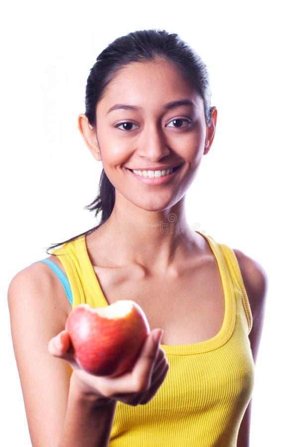 Ευτυχές ελκυστικό ινδικό κορίτσι που δίνει ένα μήλο στοκ εικόνες