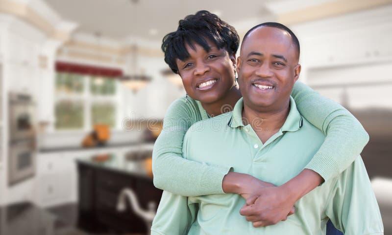 Ευτυχές ζεύγος αφροαμερικάνων μέσα στην όμορφη κουζίνα συνήθειας στοκ εικόνα