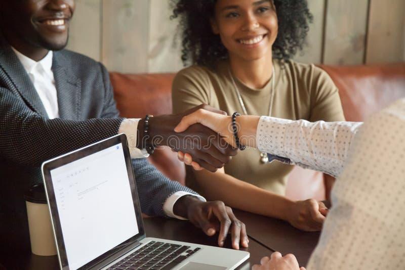Ευτυχές ζεύγος αφροαμερικάνων που καθιστά τη χειραψία διαπραγμάτευσης καυκάσια στοκ φωτογραφία