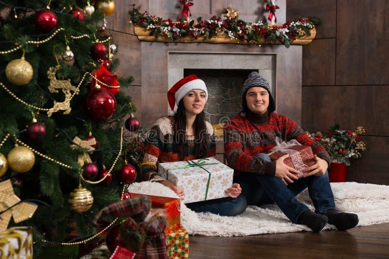 Ευτυχές ζεύγος και αστεία χειμερινά καπέλα που κρατούν τα δώρα καθμένος το ο στοκ φωτογραφία