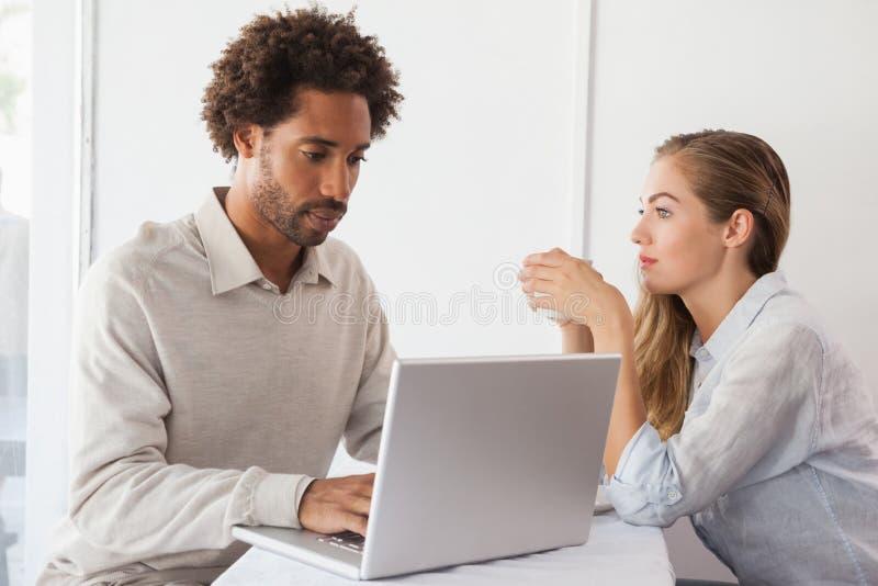 Ευτυχές ζεύγος κατά μια ημερομηνία που χρησιμοποιεί το lap-top στοκ φωτογραφία με δικαίωμα ελεύθερης χρήσης