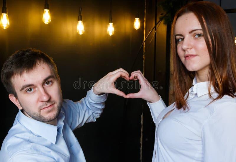 Ευτυχές ζεύγος κατά τη διάρκεια του κινούμενου σπιτιού που παρουσιάζει σημάδι καρδιών Όμορφο νέο ζεύγος που κατασκευάζει μια καρδ στοκ εικόνα με δικαίωμα ελεύθερης χρήσης