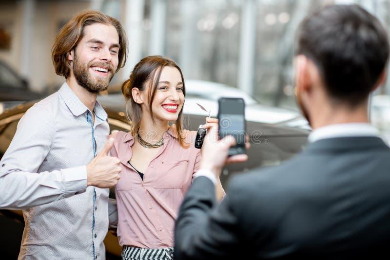 Ευτυχές ζεύγος κοντά στο νέο αυτοκίνητο στην αίθουσα εκθέσεως στοκ εικόνες με δικαίωμα ελεύθερης χρήσης