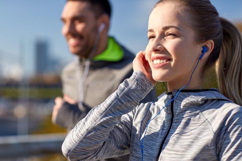 Ευτυχές ζεύγος με τα ακουστικά που τρέχουν στην πόλη στοκ φωτογραφία με δικαίωμα ελεύθερης χρήσης