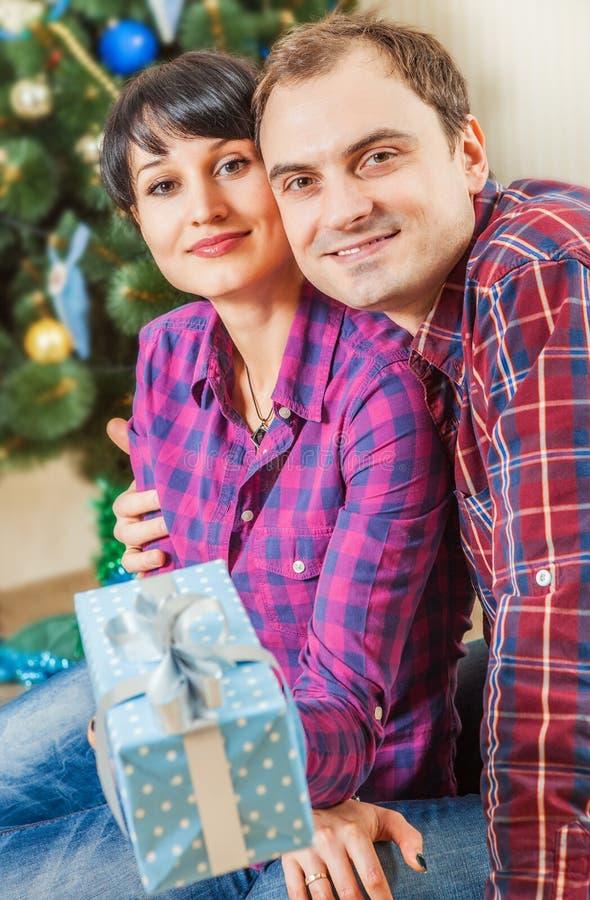 Ευτυχές ζεύγος με τα κιβώτια δώρων κάτω από το χριστουγεννιάτικο δέντρο στοκ εικόνα με δικαίωμα ελεύθερης χρήσης