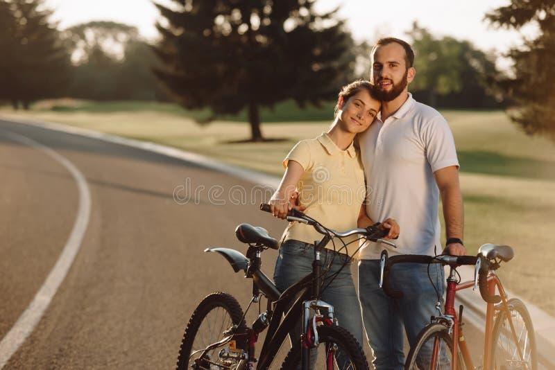 Ευτυχές ζεύγος με τα ποδήλατα υπαίθρια στοκ φωτογραφία