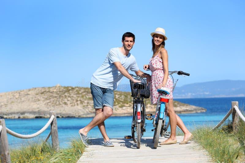 Ευτυχές ζεύγος με τα ποδήλατα που υπερασπίζονται την ακτή στοκ φωτογραφία με δικαίωμα ελεύθερης χρήσης