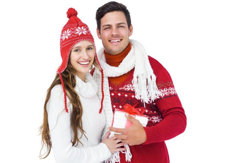 Ευτυχές ζεύγος με τα χειμερινά ενδύματα που κρατά το κιβώτιο δώρων στοκ φωτογραφία