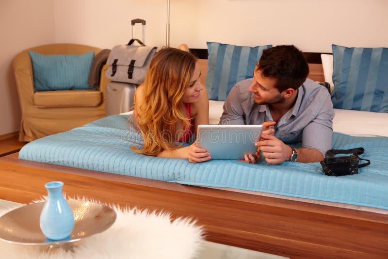 Ευτυχές ζεύγος με την ταμπλέτα στο δωμάτιο ξενοδοχείου στοκ εικόνα