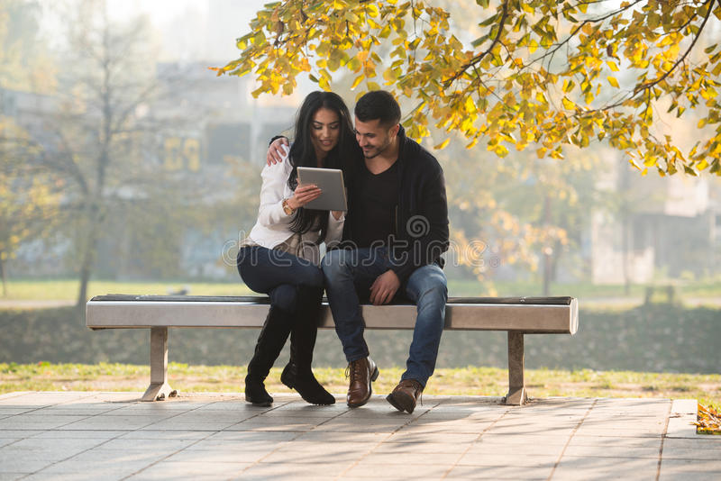 Ευτυχές ζεύγος με τον υπολογιστή ταμπλετών στο πάρκο στοκ φωτογραφίες με δικαίωμα ελεύθερης χρήσης