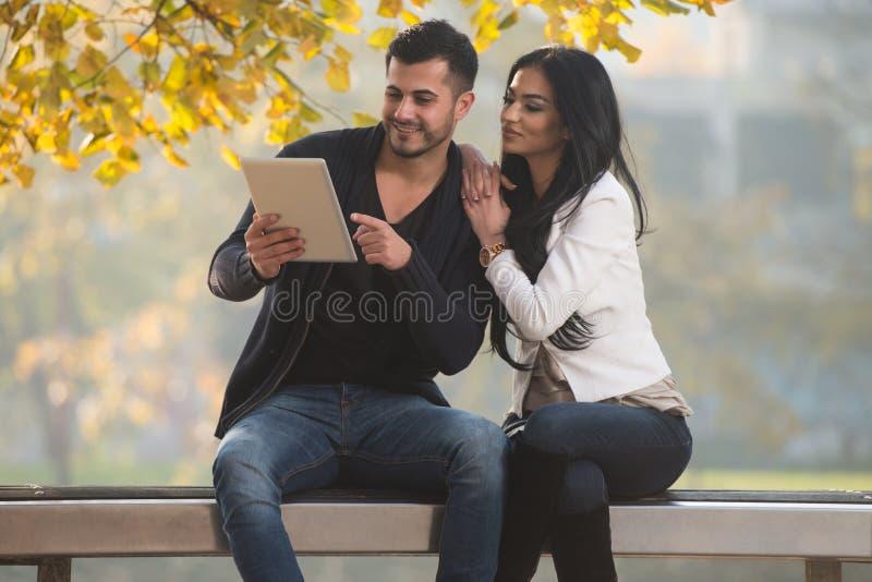 Ευτυχές ζεύγος με τον υπολογιστή ταμπλετών στο πάρκο στοκ φωτογραφίες