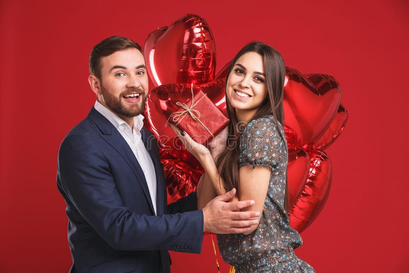 Ευτυχές ζεύγος με το δώρο και μπαλόνια σε ένα κόκκινο υπόβαθρο στοκ φωτογραφία με δικαίωμα ελεύθερης χρήσης