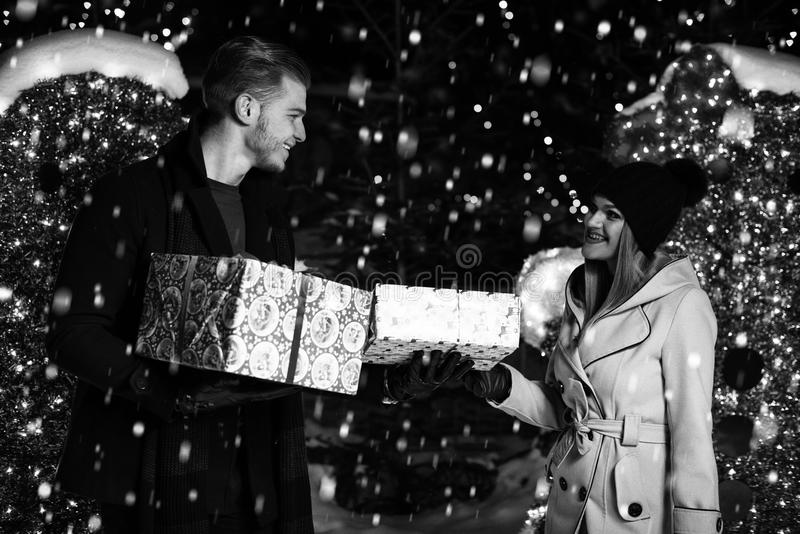 Ευτυχές ζεύγος με το κιβώτιο δώρων πέρα από τα φω'τα Χριστουγέννων στοκ εικόνες