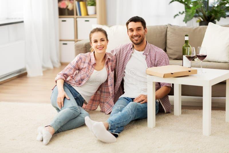 Ευτυχές ζεύγος με το κρασί και τη take-$l*away πίτσα στο σπίτι στοκ εικόνες με δικαίωμα ελεύθερης χρήσης