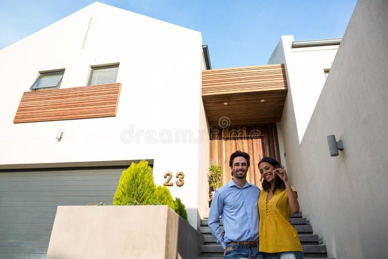 Ευτυχές ζεύγος μπροστά από το καινούργιο σπίτι που παρουσιάζει κλειδιά στοκ εικόνες