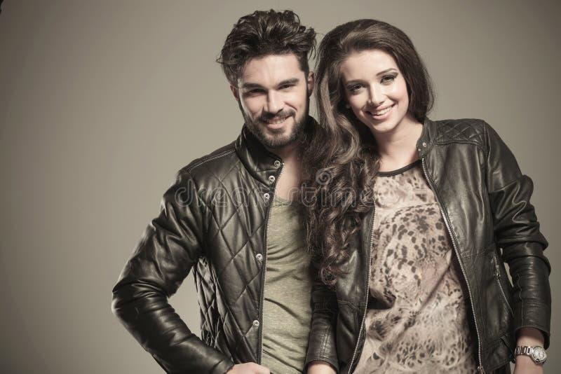 Ευτυχές ζεύγος μόδας στο χαμόγελο σακακιών δέρματος στοκ φωτογραφίες