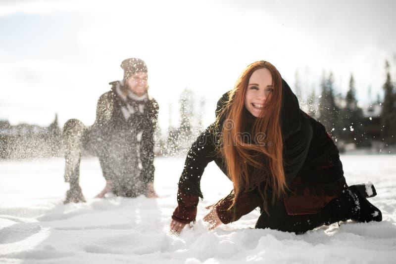 Ευτυχές ζεύγος που έχει το παιχνίδι διασκέδασης στο χιόνι στοκ εικόνα με δικαίωμα ελεύθερης χρήσης