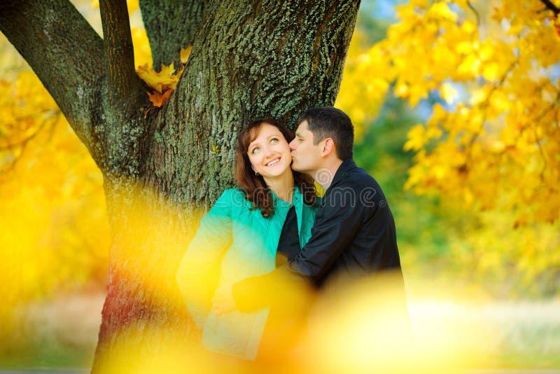 Ευτυχές ζεύγος που αγκαλιάζει και που στέκεται σε ένα όμορφο πάρκο στοκ εικόνες