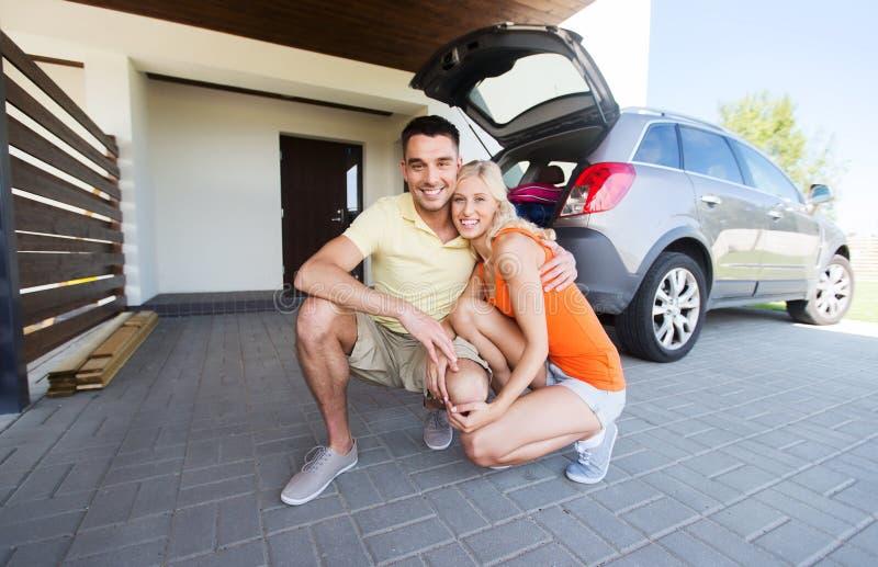 Ευτυχές ζεύγος που αγκαλιάζει στο σπίτι το διάστημα χώρων στάθμευσης αυτοκινήτων στοκ φωτογραφία