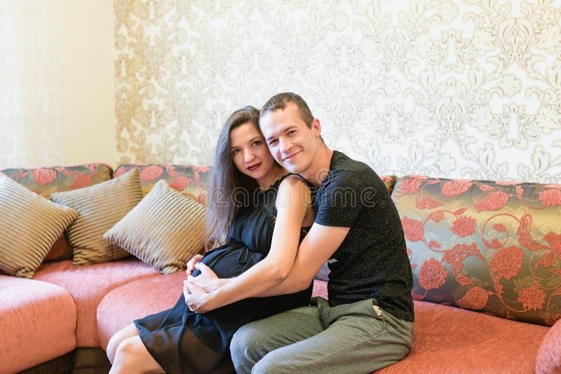 Ευτυχές ζεύγος που αναμένει ένα μωρό Ευτυχής οικογενειακός τρόπος ζωής Το νέο ζεύγος αναμένει ένα μωρό Έγκυος γυναίκα που βάζει σ στοκ φωτογραφίες με δικαίωμα ελεύθερης χρήσης
