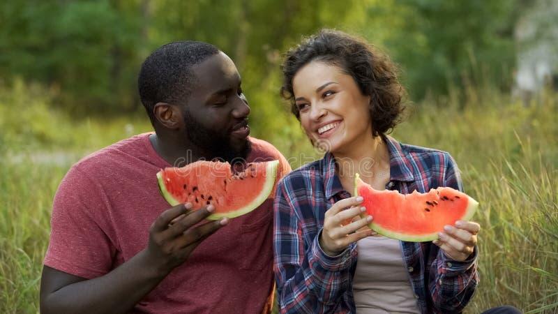 Ευτυχές ζεύγος που απολαμβάνει τις μεγάλες φέτες του yummy καρπουζιού, ευεργετική διατροφή φρούτων στοκ φωτογραφία με δικαίωμα ελεύθερης χρήσης