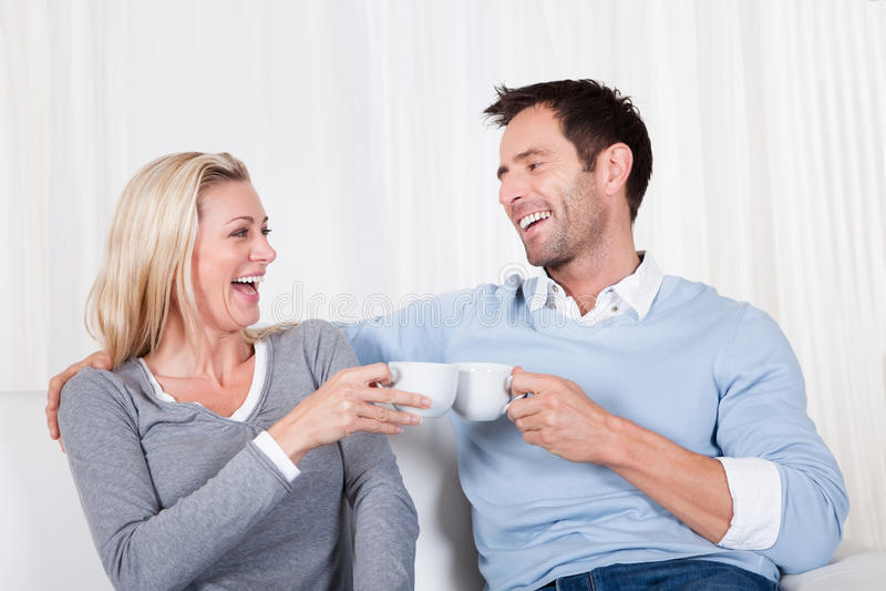 Ευτυχές ζεύγος που απολαμβάνει ένα φλυτζάνι του τσαγιού ή του καφέ στοκ φωτογραφία με δικαίωμα ελεύθερης χρήσης