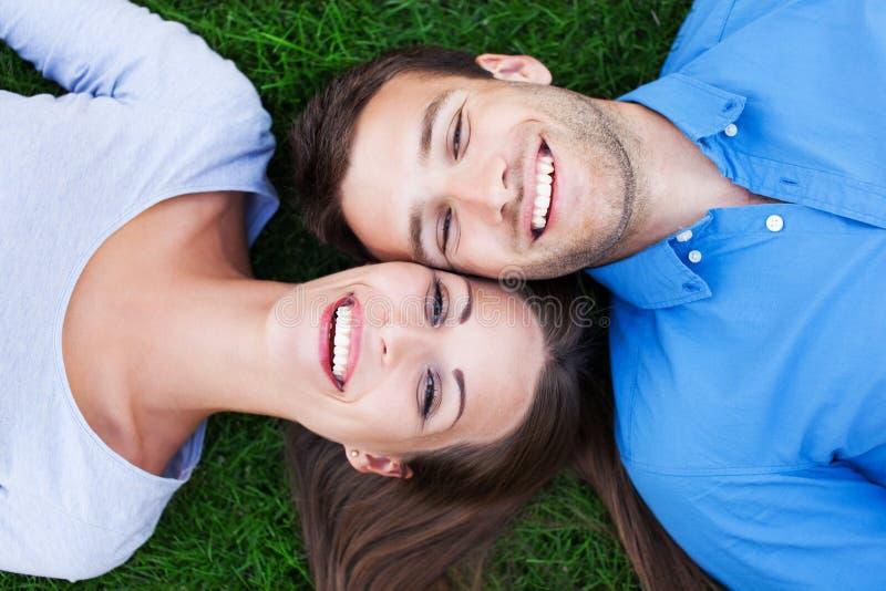 Ευτυχές ζεύγος που βρίσκεται στη χλόη στοκ φωτογραφία
