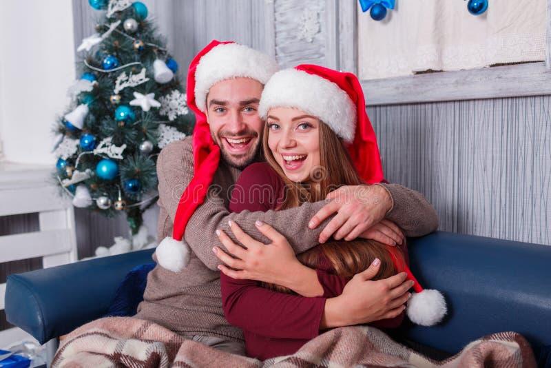 Ευτυχές ζεύγος που γελά και που αγκαλιάζει το ένα το άλλο που κάθεται στον καναπέ indoors στοκ εικόνα