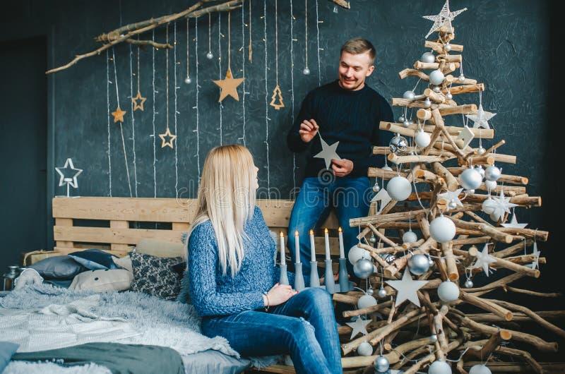 Ευτυχές ζεύγος που διακοσμεί το χριστουγεννιάτικο δέντρο στην κρεβατοκάμαρα στο σπίτι στοκ εικόνα