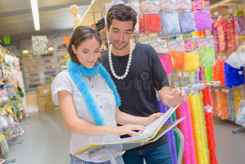 Ευτυχές ζεύγος που εξετάζει το περιοδικό εξαρτήσεων στο κατάστημα κοστουμιών στοκ εικόνα με δικαίωμα ελεύθερης χρήσης