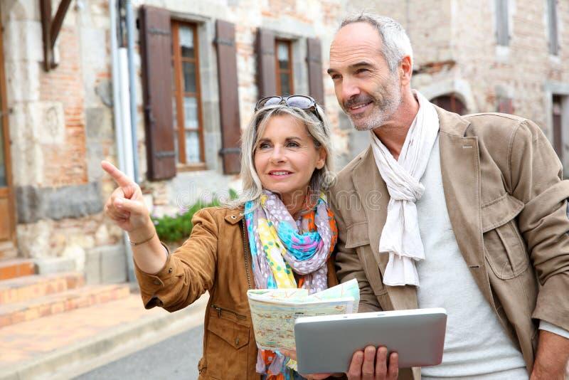Ευτυχές ζεύγος που επισκέπτεται την παλαιά πόλη με την ταμπλέτα στα χέρια στοκ φωτογραφία με δικαίωμα ελεύθερης χρήσης