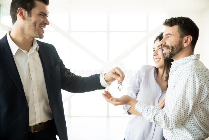 Ευτυχές ζεύγος που λαμβάνει τα κλειδιά από το μεσίτη στο νέο διαμέρισμα στοκ φωτογραφία