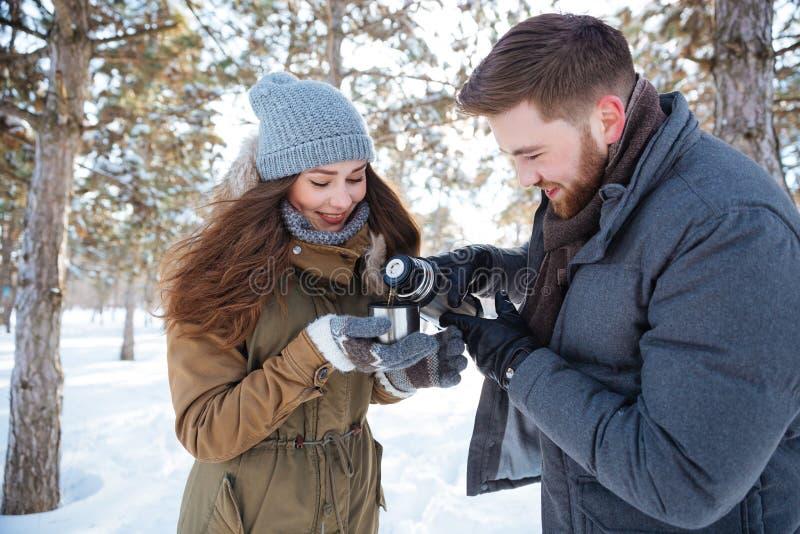 Ευτυχές ζεύγος που πίνει το καυτό τσάι στο χειμερινό πάρκο στοκ φωτογραφία με δικαίωμα ελεύθερης χρήσης