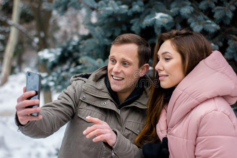 Ευτυχές ζεύγος που παίρνει την εικόνα στο smartphone πέρα από το χειμερινό υπόβαθρο στοκ εικόνες