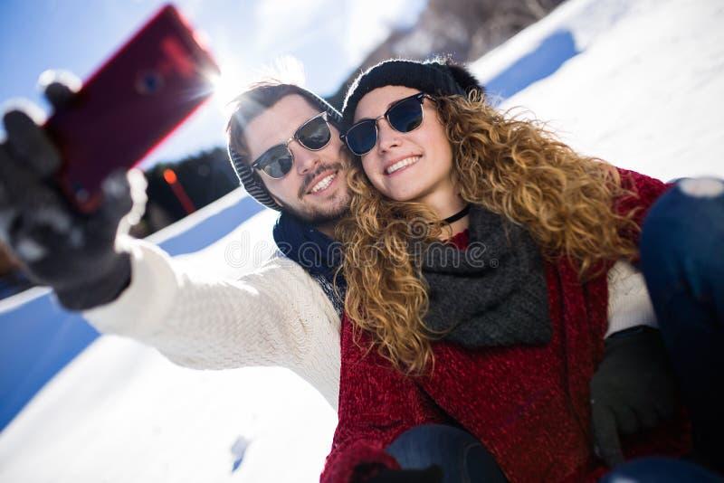 Ευτυχές ζεύγος που παίρνει selfie από το smartphone πέρα από το χειμερινό υπόβαθρο στοκ φωτογραφίες με δικαίωμα ελεύθερης χρήσης