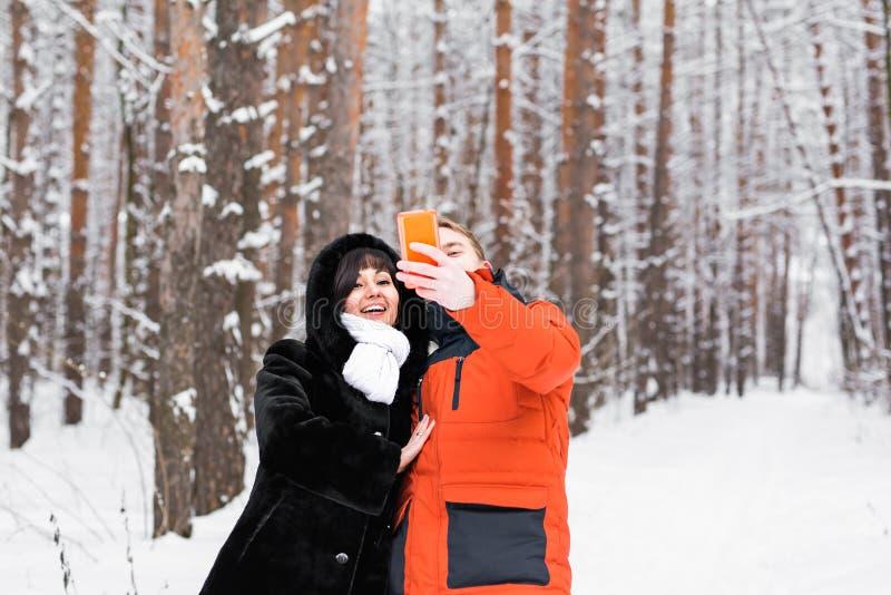 Ευτυχές ζεύγος που παίρνει selfie από το smartphone το χειμώνα στοκ εικόνες με δικαίωμα ελεύθερης χρήσης