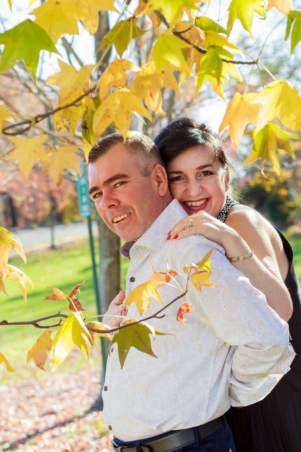 Ευτυχές ζεύγος που περπατά στο πάρκο πόλεων φθινοπώρου στοκ εικόνες