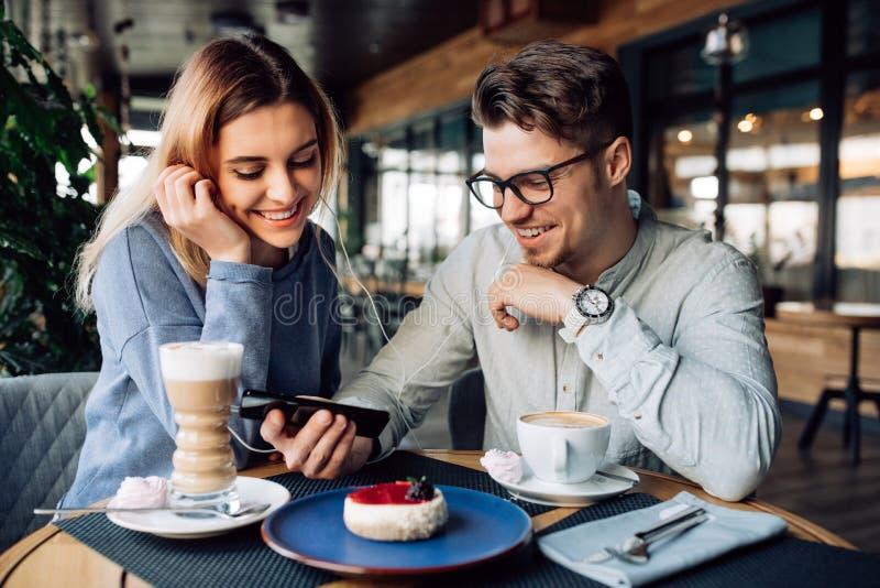 Ευτυχές ζεύγος που προσέχει έναν κινηματογράφο στο smartphone, που απολαμβάνει στηργμένος το χρόνο στον καφέ στοκ φωτογραφία