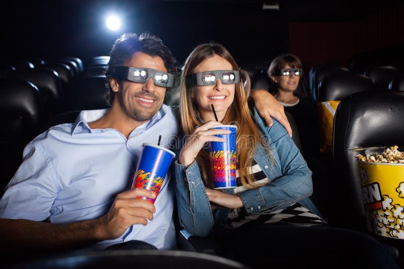 Ευτυχές ζεύγος που προσέχει την τρισδιάστατη ταινία στο θέατρο στοκ φωτογραφία
