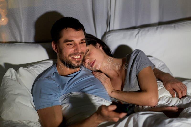 Ευτυχές ζεύγος που προσέχει τη TV στο κρεβάτι τη νύχτα στο σπίτι στοκ φωτογραφία με δικαίωμα ελεύθερης χρήσης