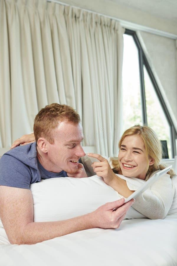 Ευτυχές ζεύγος που στηρίζεται στο κρεβάτι στοκ εικόνες με δικαίωμα ελεύθερης χρήσης