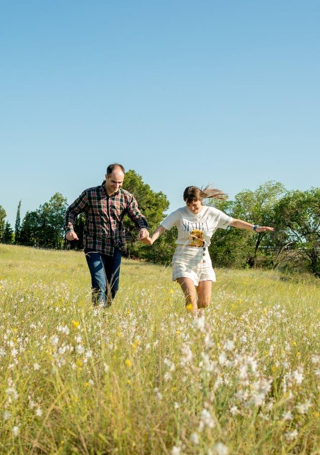 Ευτυχές ζεύγος που τρέχει σε ένα λιβάδι το καλοκαίρι στοκ φωτογραφία