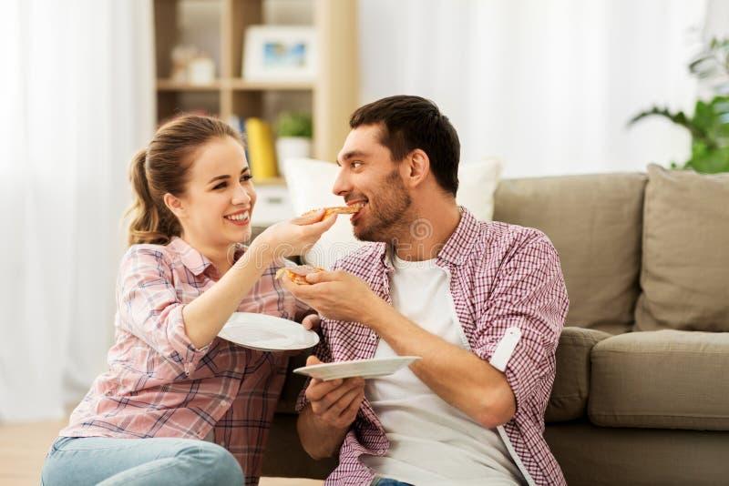 Ευτυχές ζεύγος που τρώει την πίτσα στο σπίτι στοκ εικόνες
