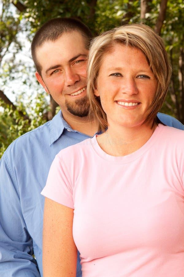 Ευτυχές ζεύγος που χαμογελά και που αγκαλιάζει στο πάρκο στοκ εικόνες