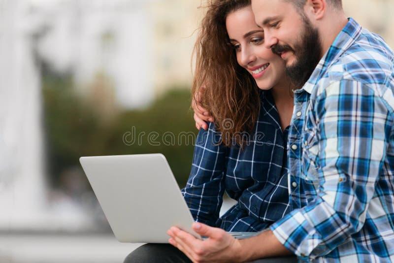 Ευτυχές ζεύγος που χρησιμοποιεί τη συνεδρίαση φορητών προσωπικών υπολογιστών στον πάγκο υπαίθρια στοκ φωτογραφία με δικαίωμα ελεύθερης χρήσης